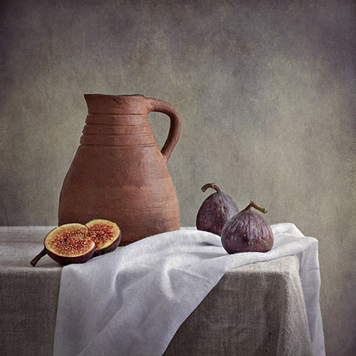 Still life photograph featuring figs and terracotta jug